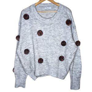 Oversized grey knit jumper with pom poms